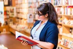 Livros de compra da mulher na livraria foto de stock