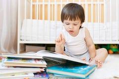 Livros de leitura agradáveis da criança contra a cama branca Fotos de Stock Royalty Free