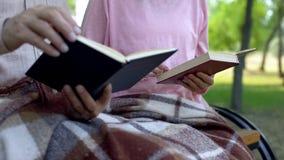 Livros de leitura aposentados dos pares, banco de parque do assento junto, tempo de lazer da pensão fotografia de stock