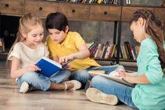Livros de leitura concentrados do menino e das meninas fotografia de stock royalty free
