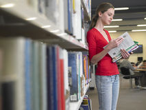 Livros de leitura da menina na biblioteca Fotos de Stock