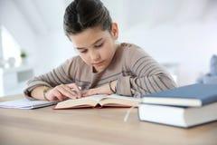 Livros de leitura da moça e trabalhos de casa fazer Fotografia de Stock Royalty Free