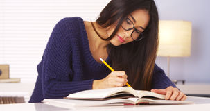 Livros de leitura da mulher e notas japoneses da tomada Fotografia de Stock Royalty Free