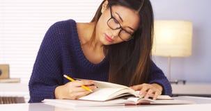 Livros de leitura da mulher e notas japoneses da tomada Imagens de Stock Royalty Free