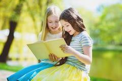 Livros de leitura das crianças no parque Meninas que sentam-se contra árvores e lago exterior Fotos de Stock Royalty Free