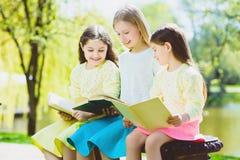 Livros de leitura das crianças no parque Meninas que sentam-se contra árvores e lago exterior Fotografia de Stock Royalty Free