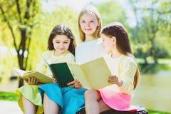 Livros de leitura das crianças no parque Meninas que sentam-se contra árvores e lago exterior Imagens de Stock Royalty Free