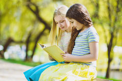 Livros de leitura das crianças no parque Meninas que sentam-se contra árvores e lago exterior Imagens de Stock