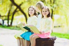 Livros de leitura das crianças no parque Meninas que sentam-se contra árvores e lago exterior Imagem de Stock Royalty Free