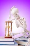 Livros de leitura de esqueleto contra o inclinação Imagens de Stock