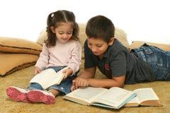 Livros de leitura do irmão e da irmã no assoalho foto de stock