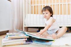 Livros de leitura do menino da criança contra a cama branca Imagens de Stock Royalty Free