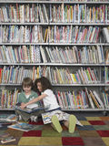 Livros de leitura do menino e da menina na biblioteca Fotos de Stock