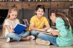 Livros de leitura do menino e das meninas imagens de stock royalty free