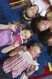 Livros de leitura dos estudantes ao encontrar-se no tapete fotos de stock