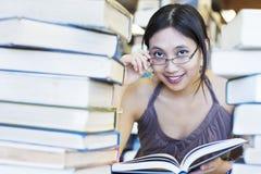 Livros de leitura felizes do estudante na biblioteca Fotos de Stock