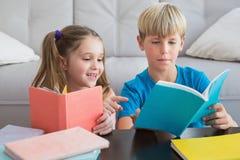 Livros de leitura felizes dos irmãos no assoalho Fotos de Stock