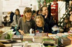 Livros de leitura não identificados das meninas na cabine das crianças do 6o ARSENAL internacional do LIVRO do festival Fotografia de Stock
