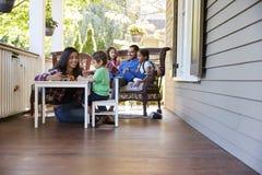 Livros de leitura de Sit On Porch Of House da família e jogos do jogo imagens de stock royalty free