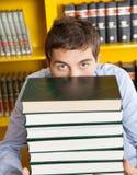 Livros de Peeking Over Stacked do estudante masculino na biblioteca imagens de stock