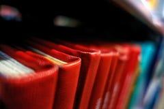 Livros de referência vermelhos nas pilhas de uma biblioteca imagem de stock