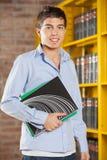 Livros de Smiling While Holding do estudante na faculdade Fotografia de Stock Royalty Free