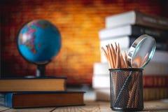 Livros de texto, globo e lápis em um fundo de madeira Fundo educacional fotografia de stock royalty free