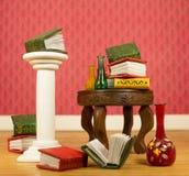 Livros diminutos e vasos na tabela Fotografia de Stock