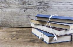 Livros e fone de ouvido colocados na tabela de madeira imagens de stock