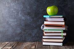Livros e maçã na frente da placa de giz imagem de stock