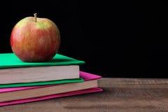 Livros e uma maçã em uma tabela de madeira em um fundo preto Conceito da instrução fotos de stock