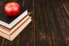 Livros e uma ma?? na tabela de madeira Teacher' conceito do dia de s e de volta ? escola imagens de stock