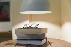 Livros em uma tabela sob uma lâmpada imagens de stock