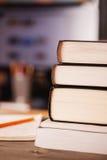 Livros empilhados na mesa Imagens de Stock