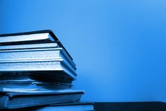 Livros empilhados no lado esquerdo da foto Tom azul macio fotos de stock royalty free