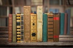 Livros empilhados velhos no fundo de madeira Imagens de Stock