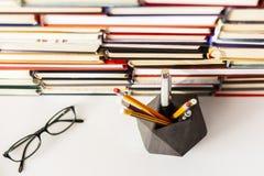 Livros fundo, vidros, lápis e pena na tabela de madeira branca imagens de stock royalty free