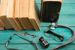 Livros médicos velhos com estetoscópio, vidros, garrafa e chave em b fotos de stock royalty free