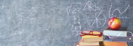 Livros, maçã, especs. na frente de uma placa preta, de volta à escola fotografia de stock royalty free