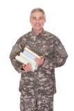 Livros maduros de Holding Stack Of do soldado fotos de stock