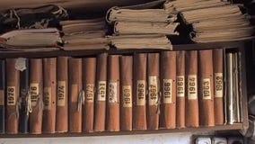 Livros marrons velhos na prateleira, fim acima da vista Câmera que move-se ao longo da estante que pendura na parede da vertente  vídeos de arquivo