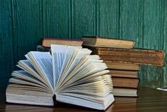 Livros na tabela perto da parede de madeira verde fotografia de stock royalty free