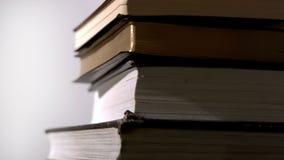 Livros negros pesados que caem na superfície do branco vídeos de arquivo