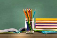 Livros, pena, lápis e equipamento de escritório na placa verde, educação e de volta ao assunto de escola, trajeto de grampeamento fotos de stock royalty free