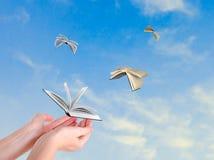 Livros que voam das mãos fotografia de stock royalty free