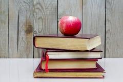 Livros velhos com maçã em um fundo branco fotos de stock