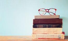 Livros velhos com vidros do vintage em uma tabela de madeira imagem filtrada retro Fotografia de Stock Royalty Free
