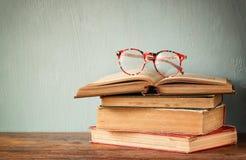 Livros velhos com vidros do vintage em uma tabela de madeira imagem filtrada retro Foto de Stock