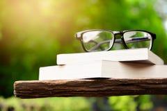 Livros velhos com vidros em uma tabela Fotografia de Stock