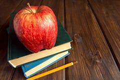 Livros velhos e maçã vermelha Imagens de Stock